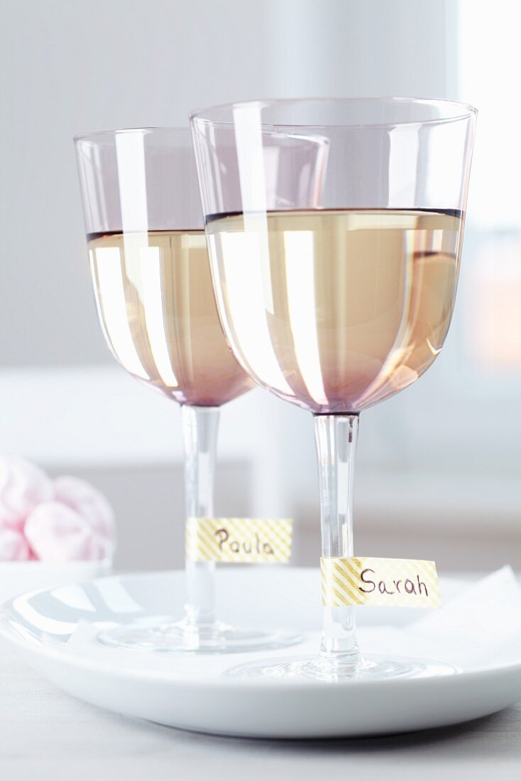 Wine glasses with names written on masking tape around the stem
