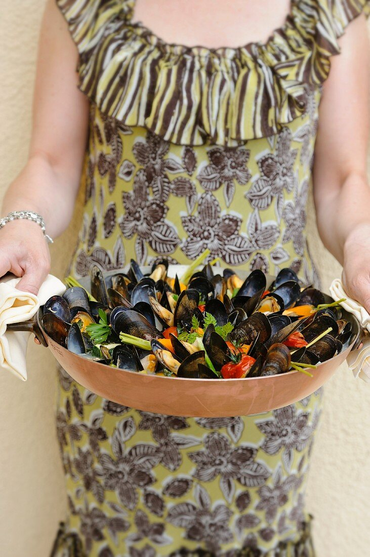 A woman serving mussels with vegetables (Normandy, France)