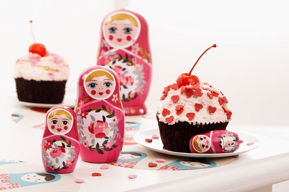 Russian dolls and a cupcake decorated with cherries and heart-shaped sprinkles