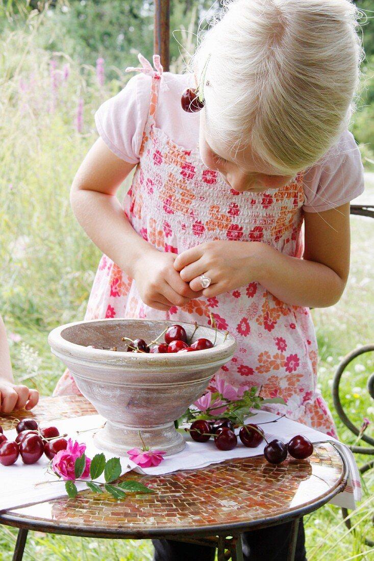 Little blond girl with cherries in a garden