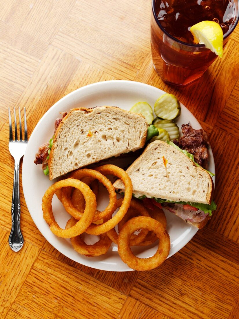 Steak Sandwich on Rye with Onion Rings and Iced Tea