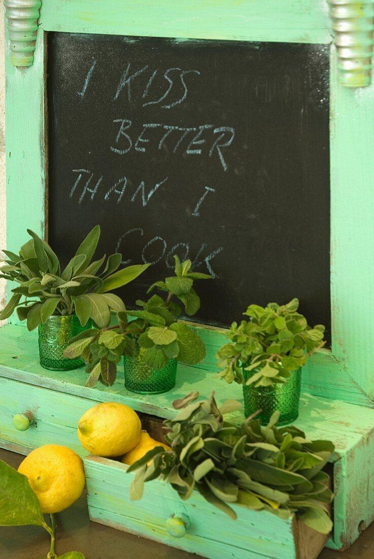 Frische Kräuter und Zitronen auf Ablage aus Holz mit türkisem Anstrich und eingebauter Schiefertafel