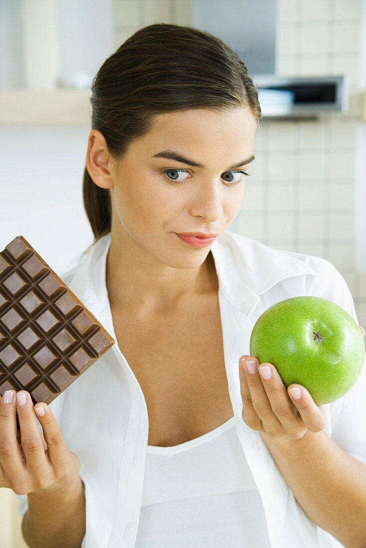 Young woman holding apple in one hand and large bar of chocolate in the other