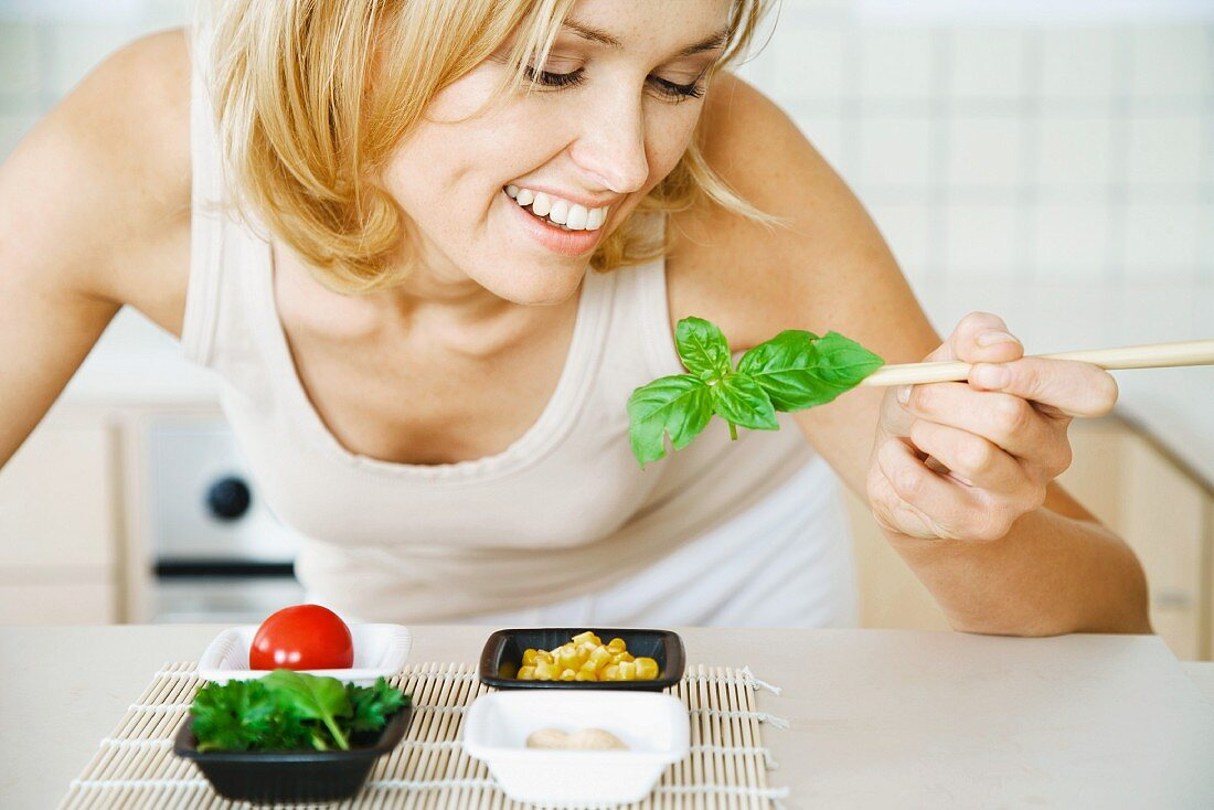 Woman leaning over, holding fresh basil with chopsticks, smiling