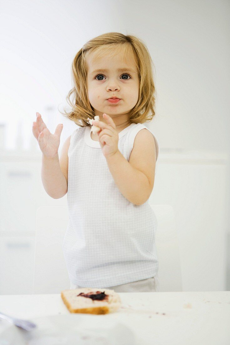 Toddler girl standing on chair, eating bread with jam