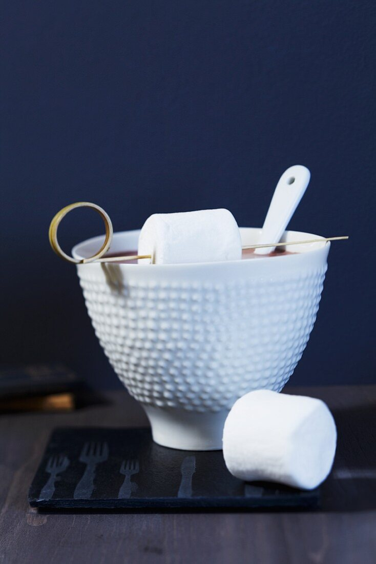 A bowl of cocoa with marshmallows on a bamboo stick