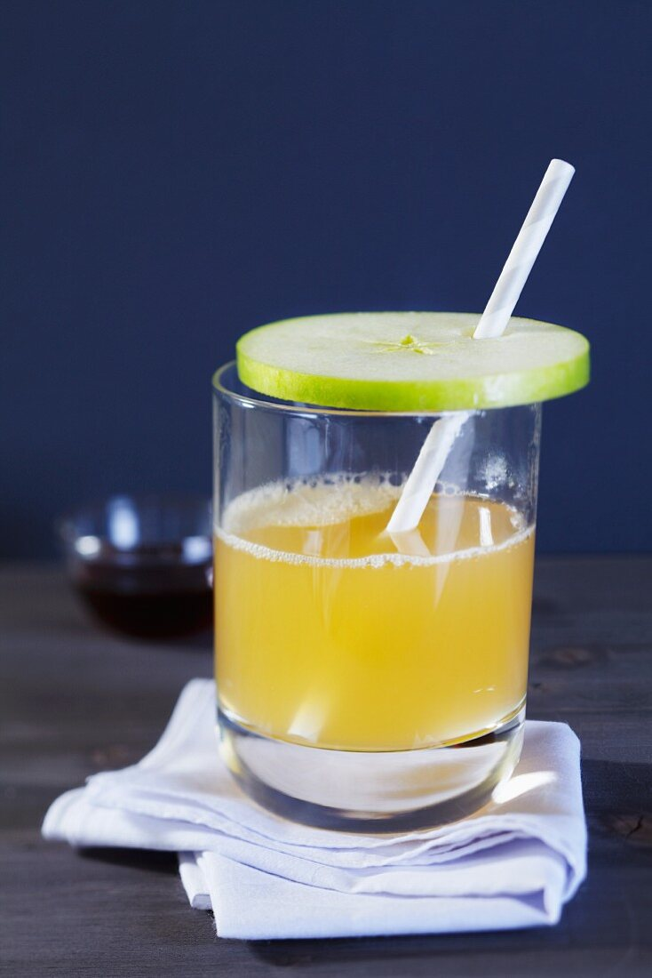 A glass of apple punch with a straw and a slice of apple as a lid