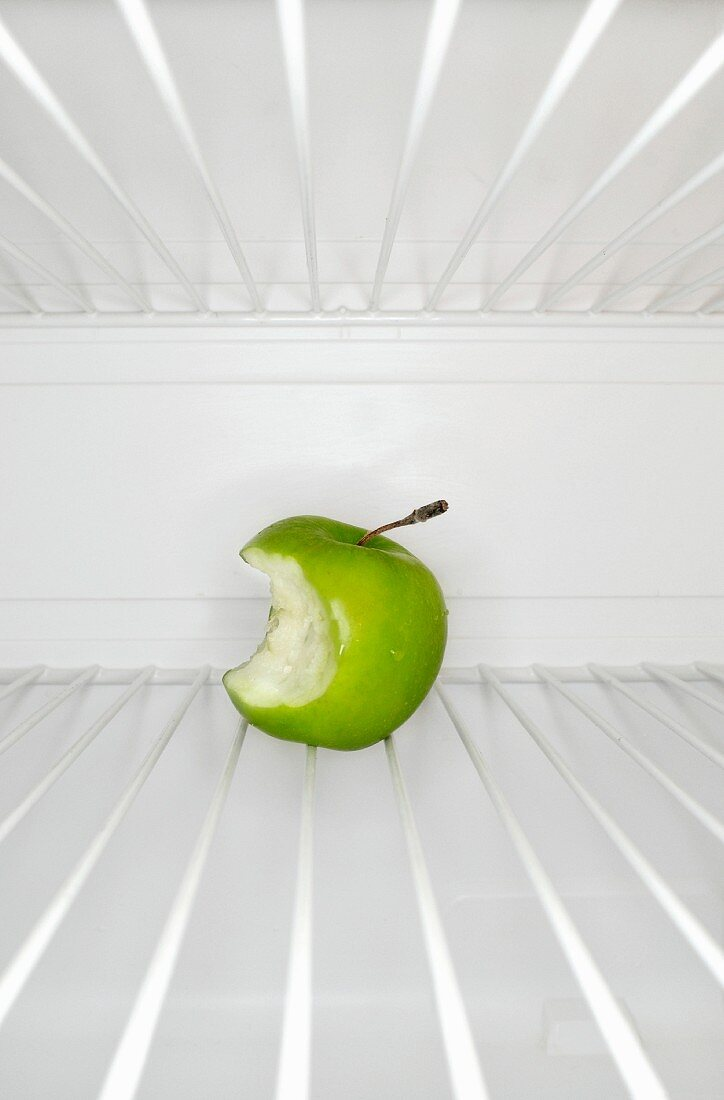 Single apple with bite mark sitting on shelf inside refrigerator