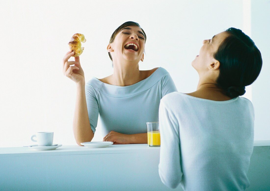 Two women on either side of bar having breakfast, laughing