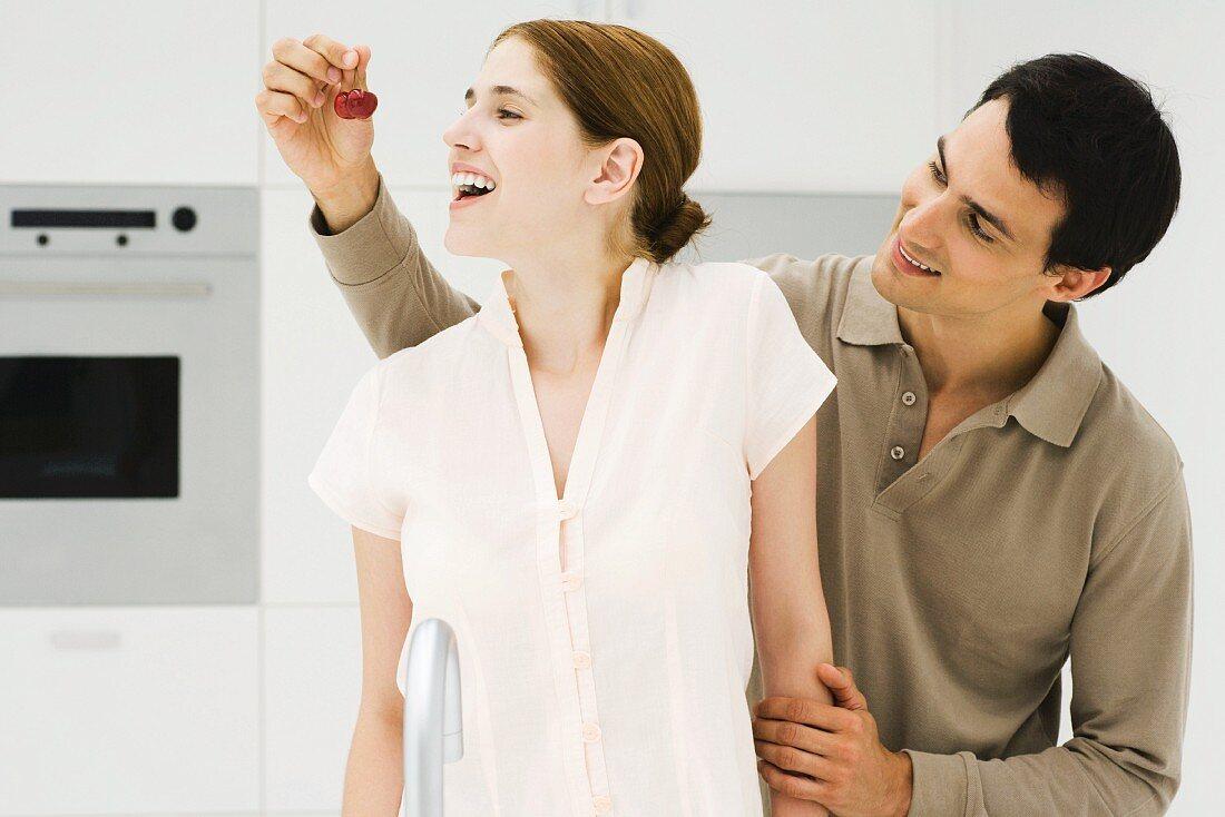 Man feeding woman cherry, both smiling, looking away