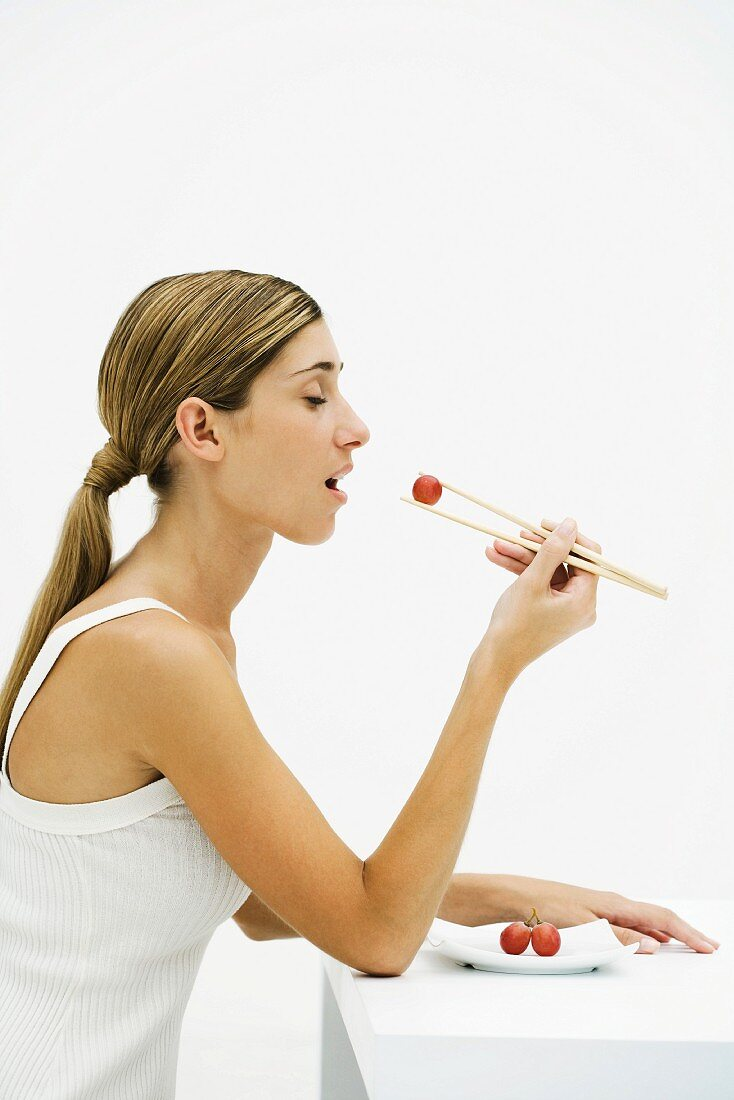 Woman eating red grape with chopsticks, eyes closed, side view