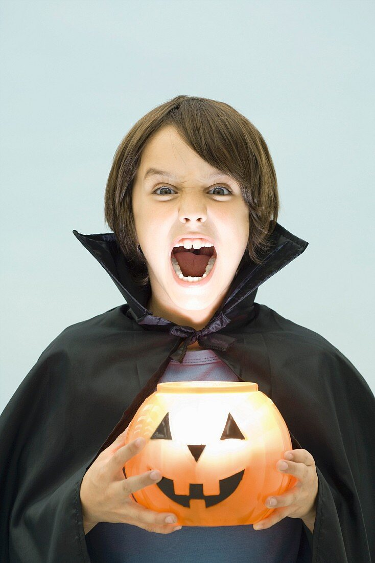 Boy holding jack o' lantern, looking at camera, open mouth, portrait