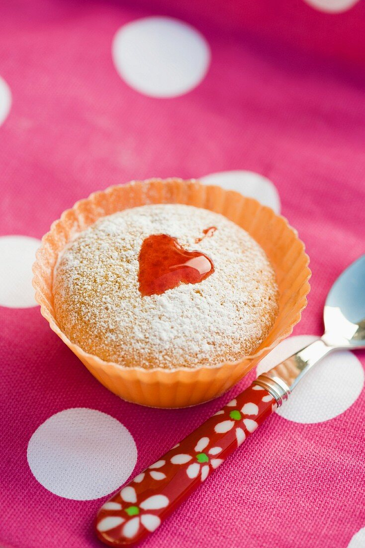 Bizcocho (a sweet cake from Spain) decorated with icing sugar and a jam heart