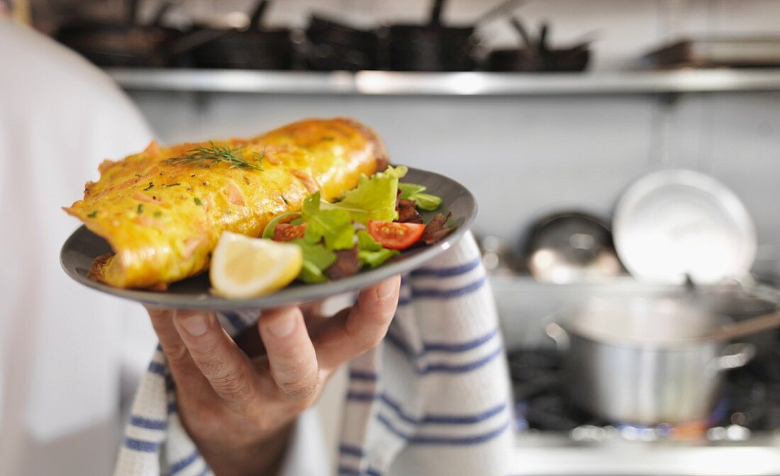 A cook holding a plate of salmon omelette and salad