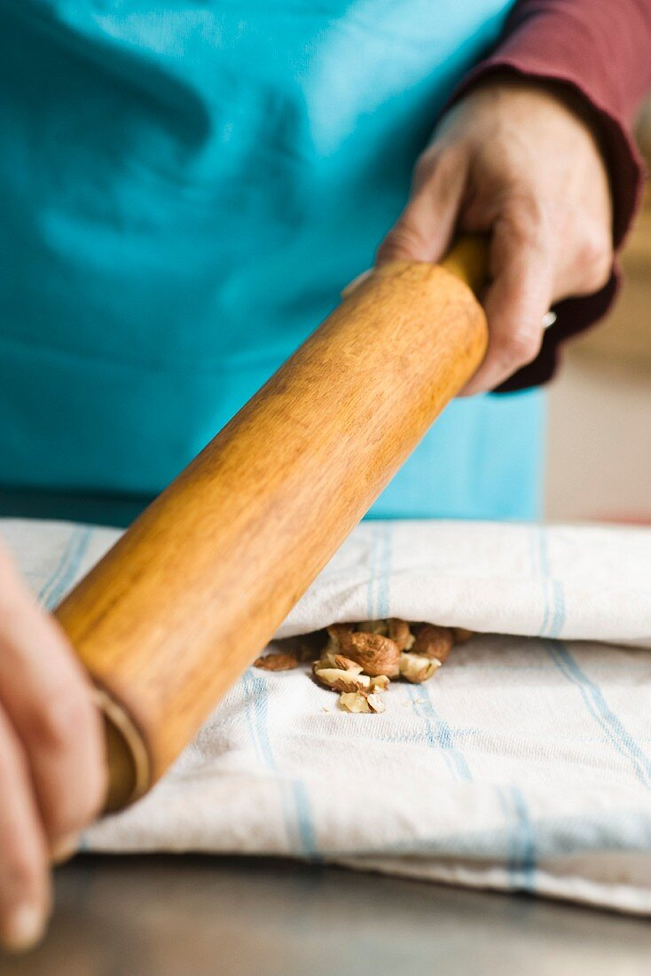 Hazelnuts being crushed with a rolling pin