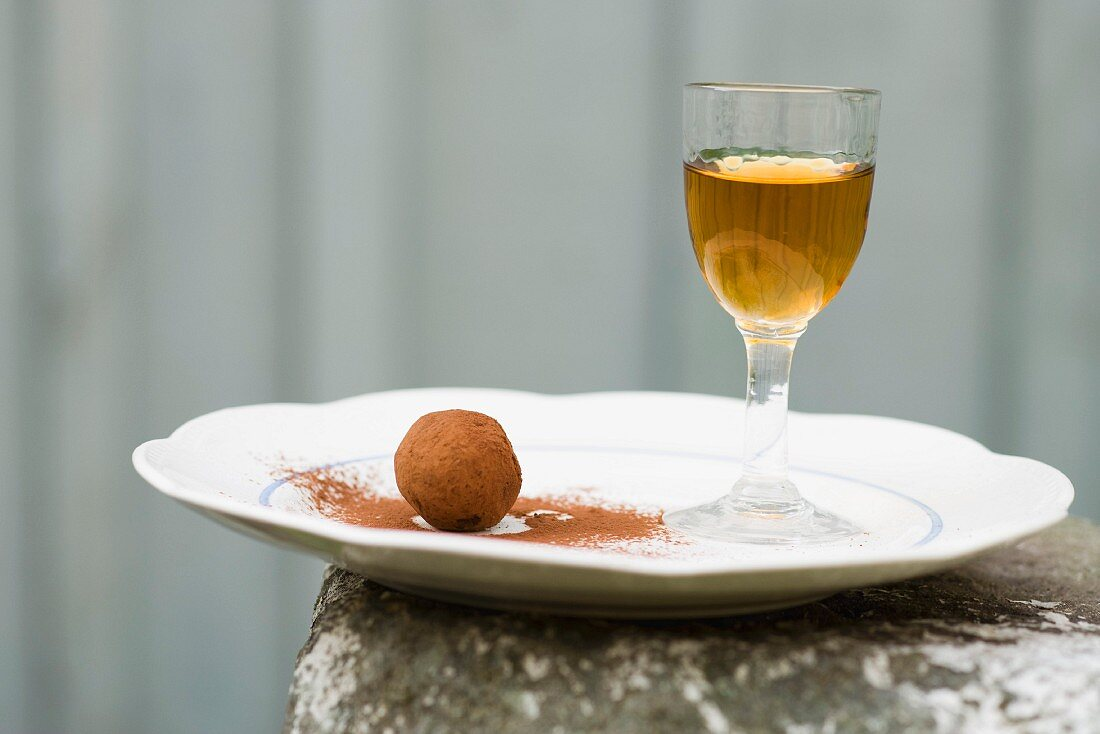 A chocolate truffle and a glass of liqueur