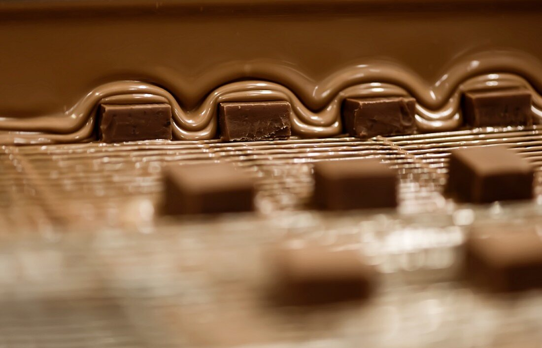 Squares of praline being covered with chocolate