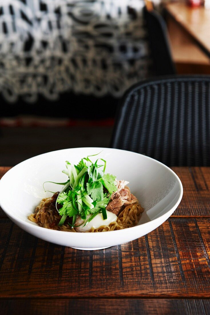 Egg noodles with duck, poached egg and coriander leaves (Asia)