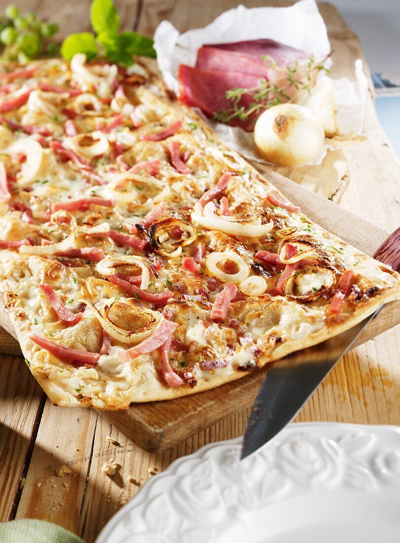 Tart flambé topped with bacon and onion rings