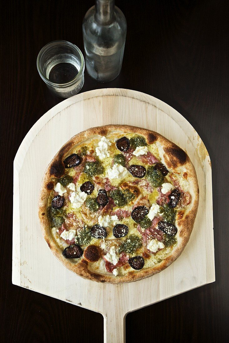 Pizza Topped with Figs, Goat Cheese, Pancetta and Pest; On a Pizza Paddle; From Above