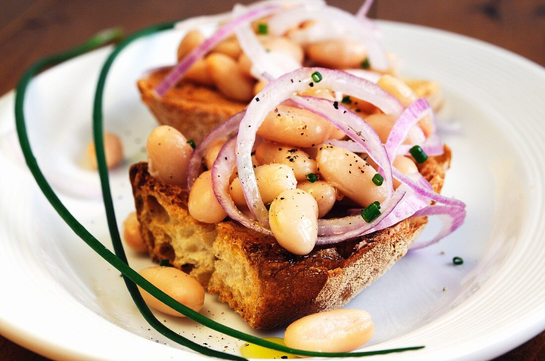 Bruschetta ai fagioli (toasted bread topped with beans and onions)