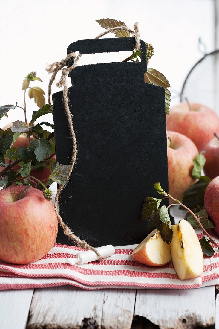 A blackboard with chalk and fresh apples