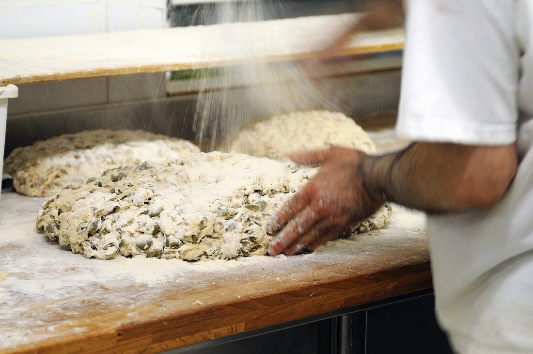 Unbaked olive bread being dusted with flour