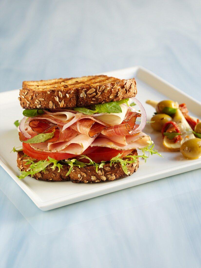 Turkey, Prosciutto and Provolone Sandwich on Grilled Whole Grain Bread with Onion, Lettuce and Tomato; Antipasti