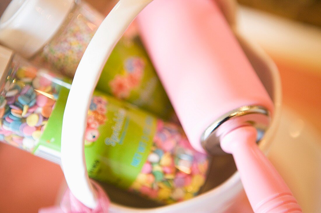 Pink rolling pin in a basket with sprinkles close up