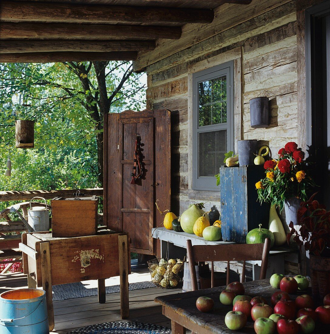A rustic veranda outside a wooden cabin with freshly picked garden fruits and a bunch of summer flowers