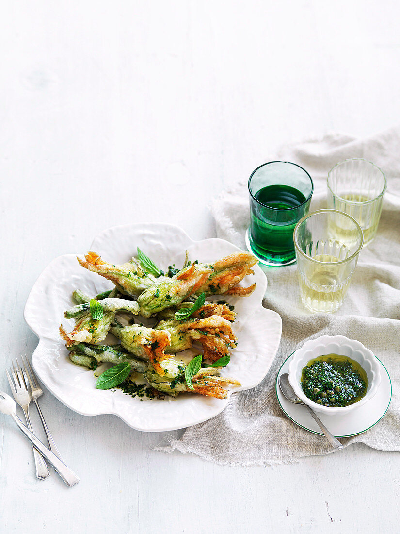 Deep-fried courgette flowers with ricotta, parmesan, and mint and anchovy sauce