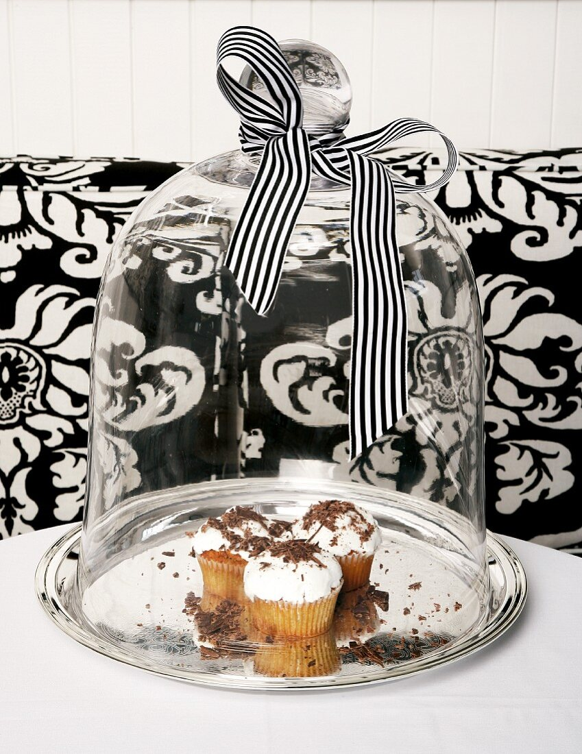 Cupcakes topped with whipped cream and grated chocolate under a glass cloche
