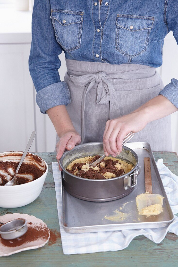Marble cake mixture being mixed in a springform tin