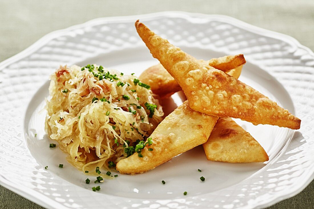 Blattlkrapfen (deep-fried batter cakes, Austria) with bacon and cabbage salad
