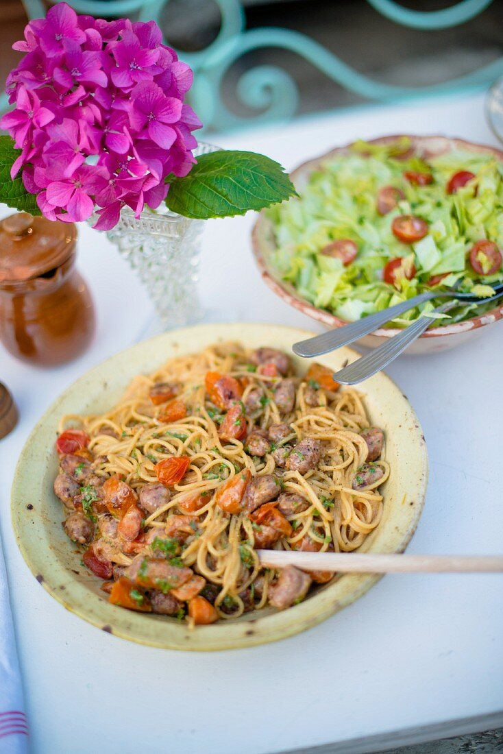 Spaghetti with meatballs and a green salad with cherry tomatoes