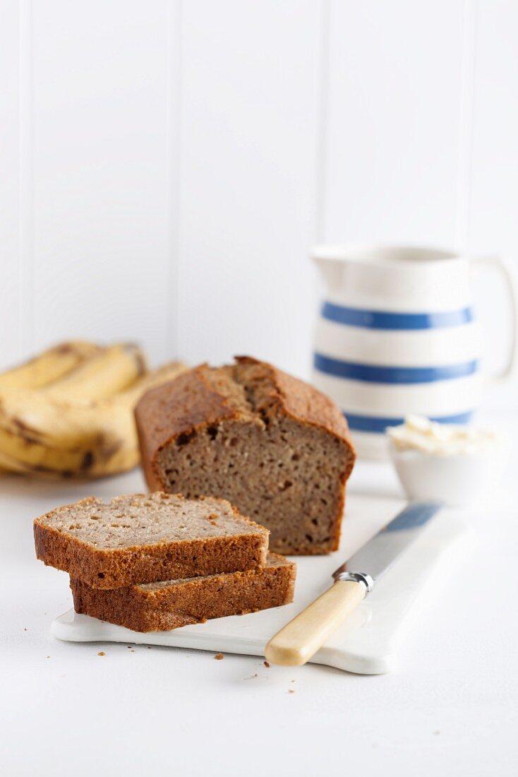 Freshly baked banana bread, sliced, on a porcelain board