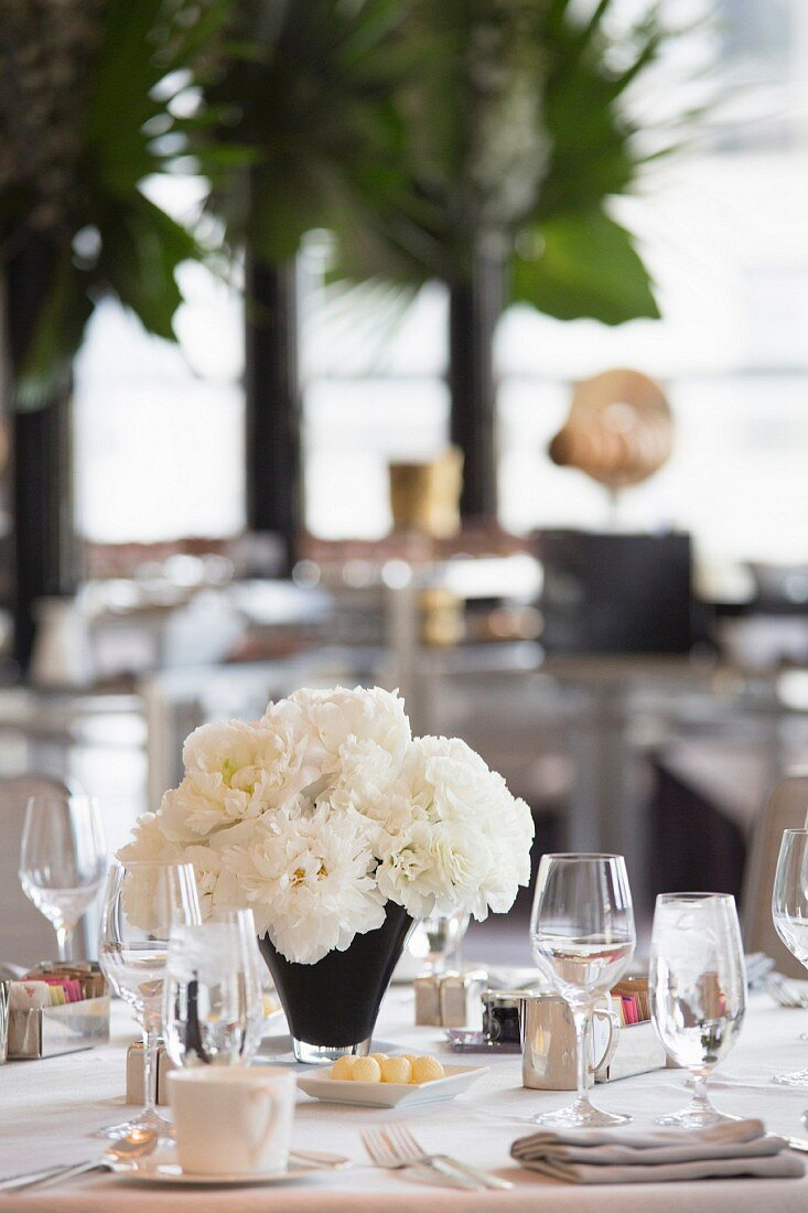 A table laid in white at a wedding reception with a bunch of white flowers