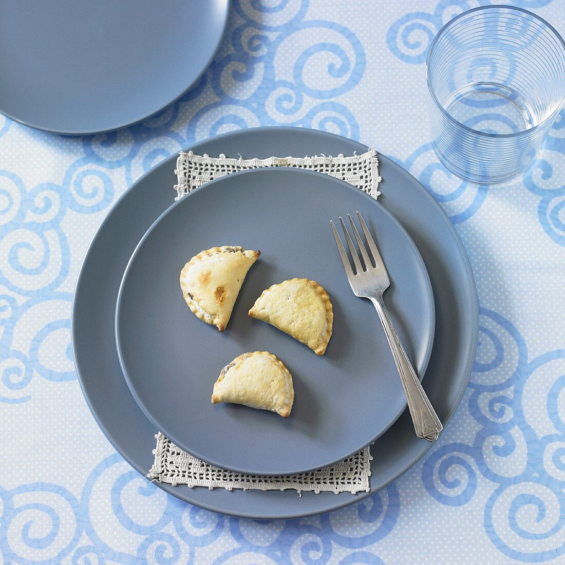 A place setting with blue plates and mushroom filled pastry parcels