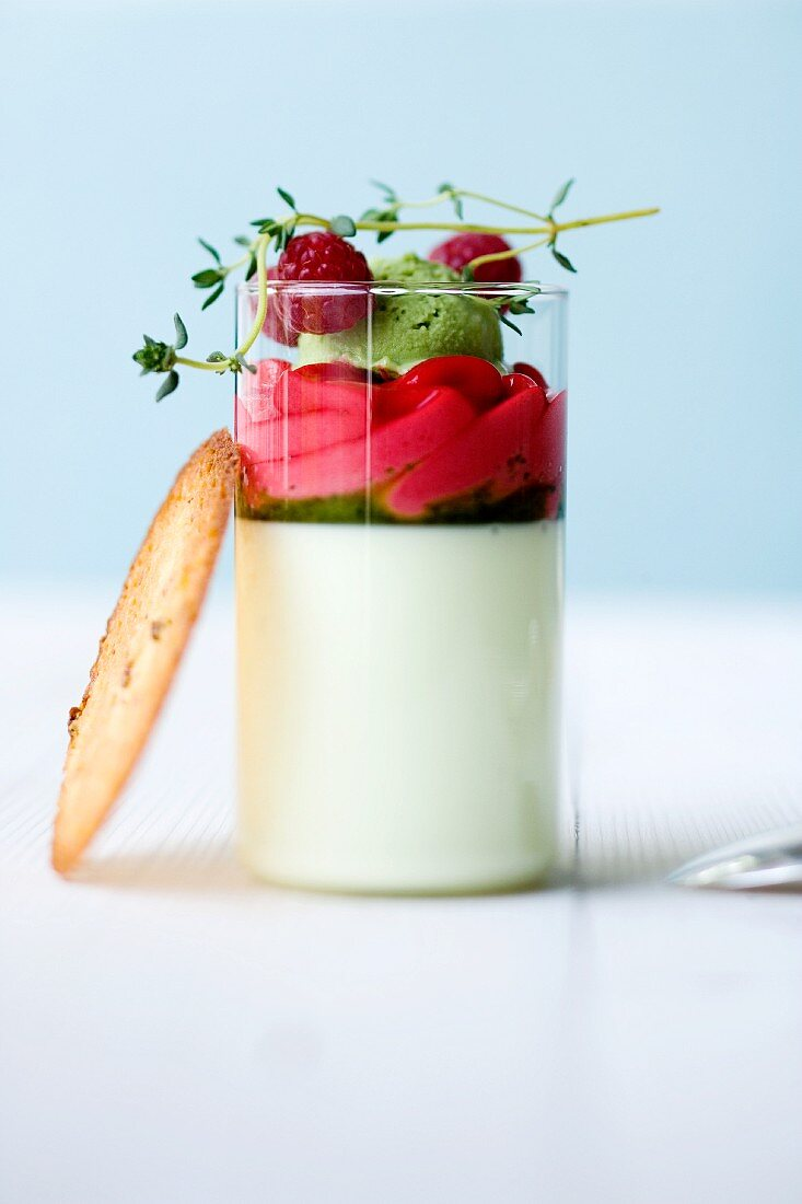 Yoghurt and thyme panna cotta with raspberry foam and herb-honey sorbet in a glass