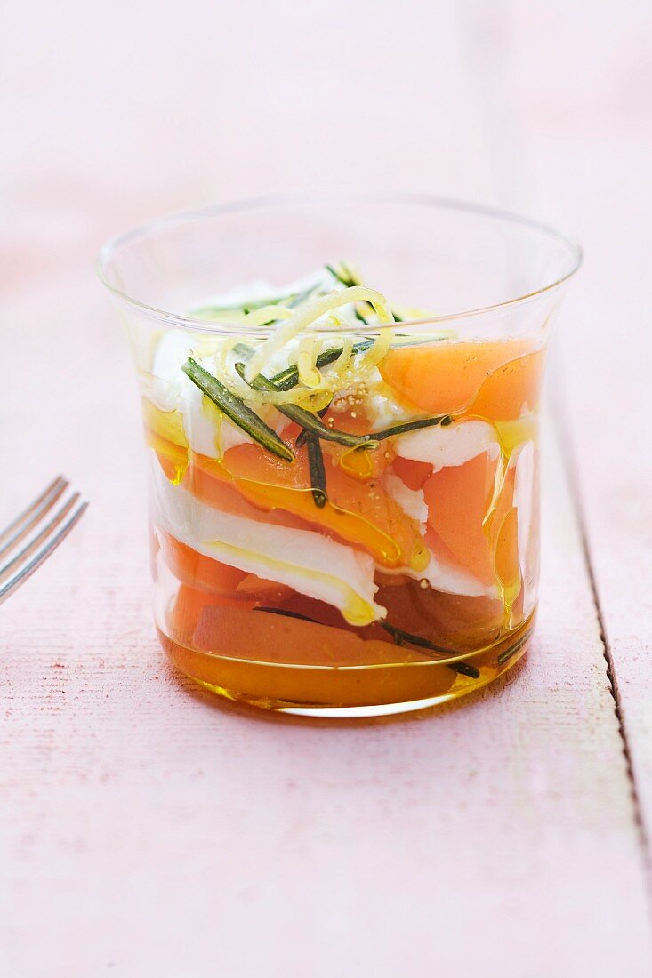 Buffalo mozzarella marinated in rosemary with apricots and lemon oil in a glass