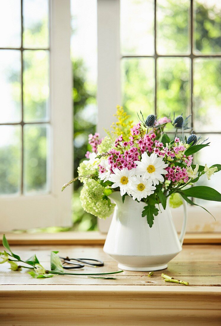 A bunch of fresh cut summer flowers in a white vase