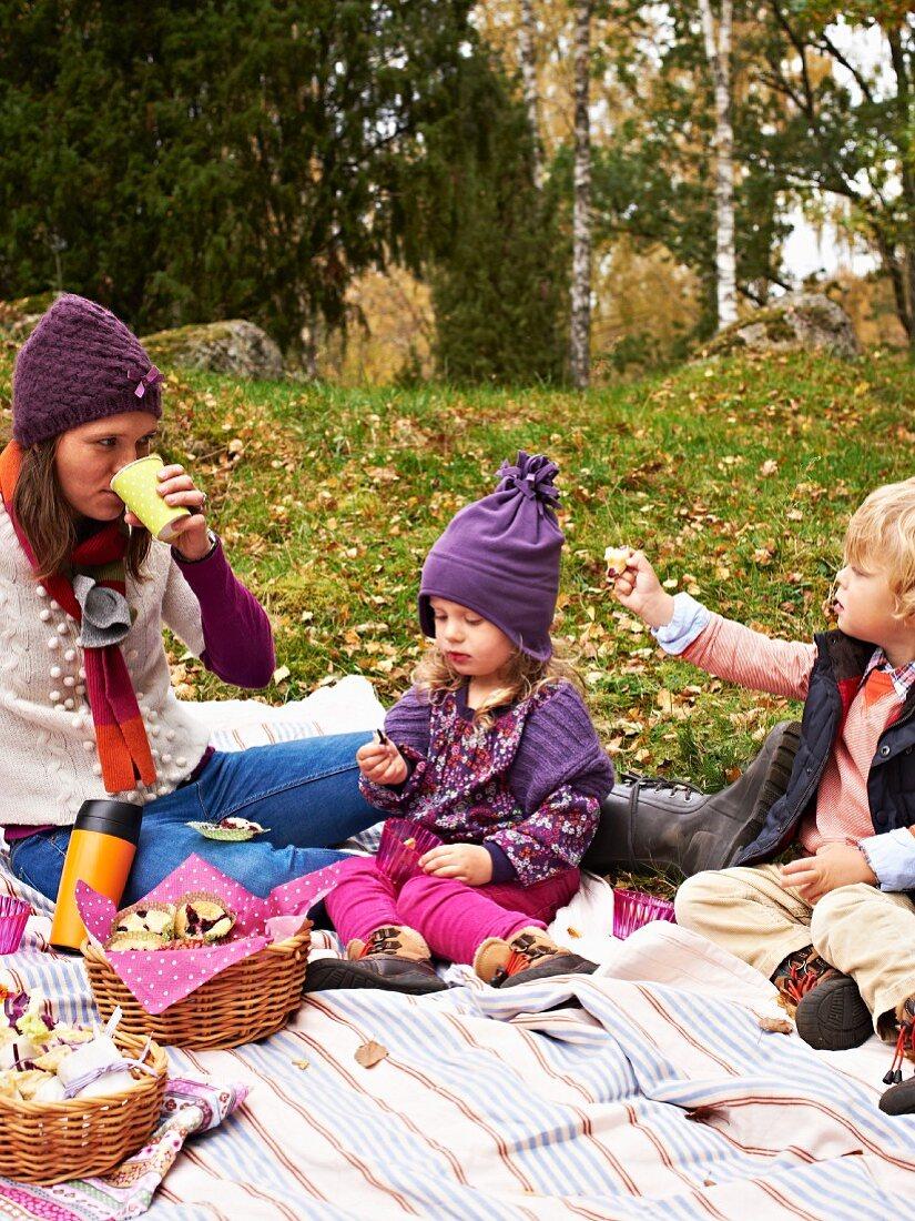 Mother and children enjoying an autumn woodland picnic