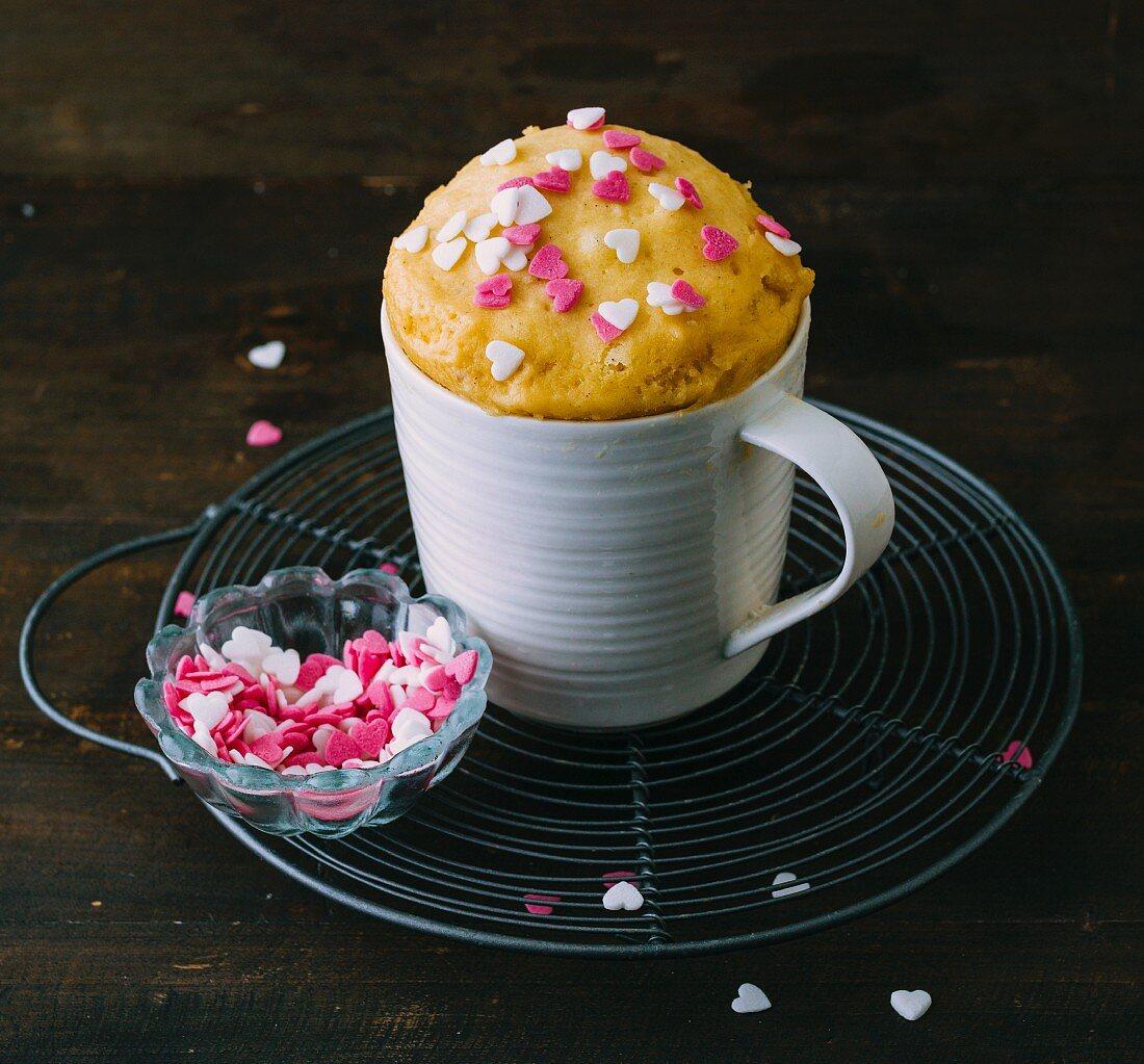 A basic mug cake decorated with sugar hearts