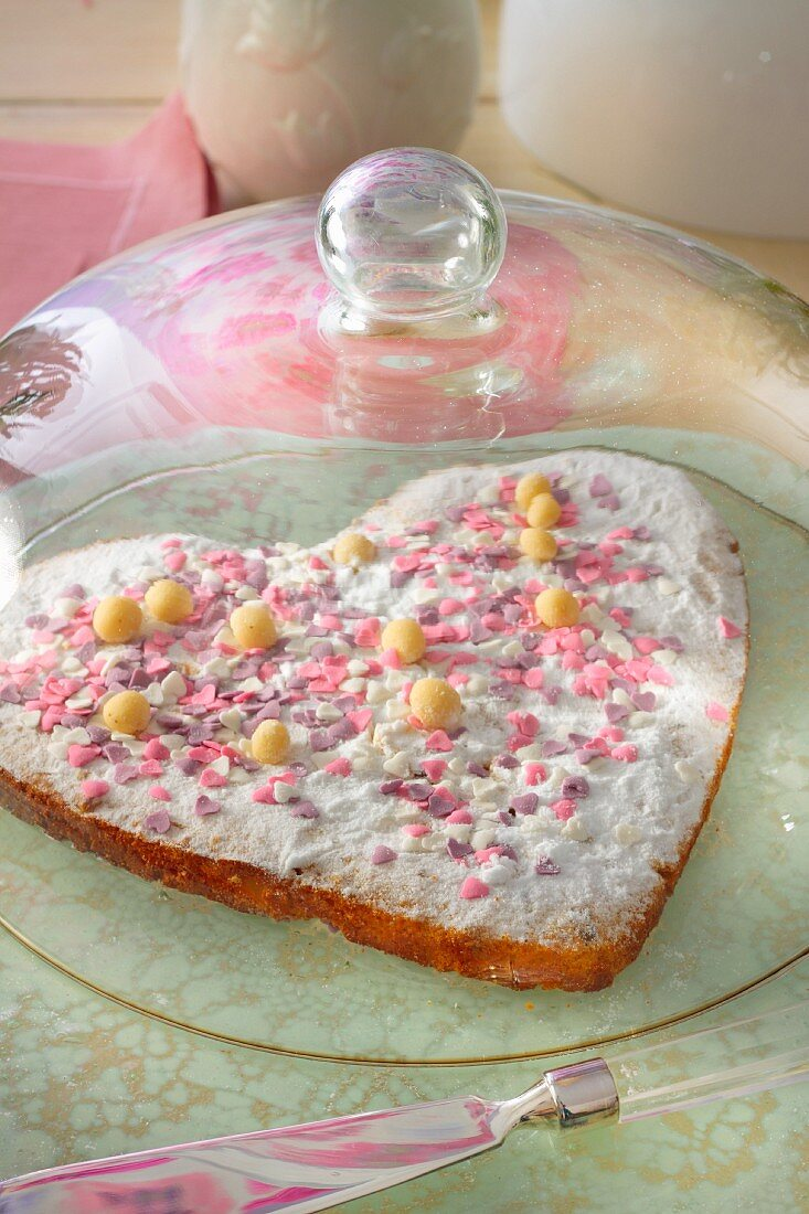 A heart-shaped cake decorated with pink sugar hearts under a glass cloche
