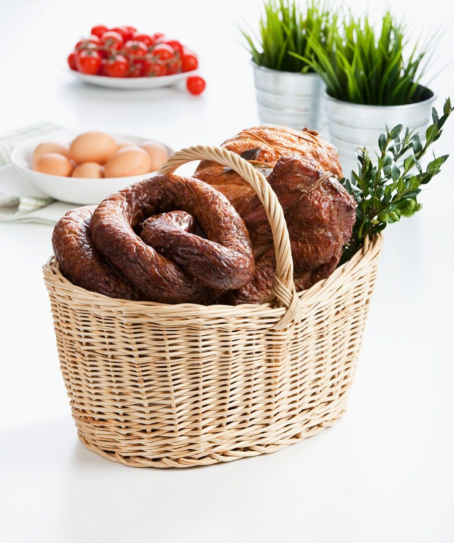 Various sausages and ham in an Easter basket