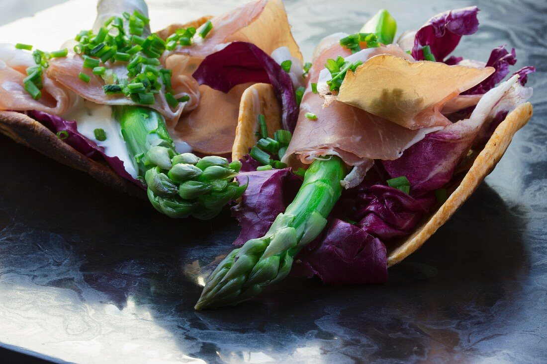 Tacos filled with green asparagus, rad cabbage and San Daniele ham