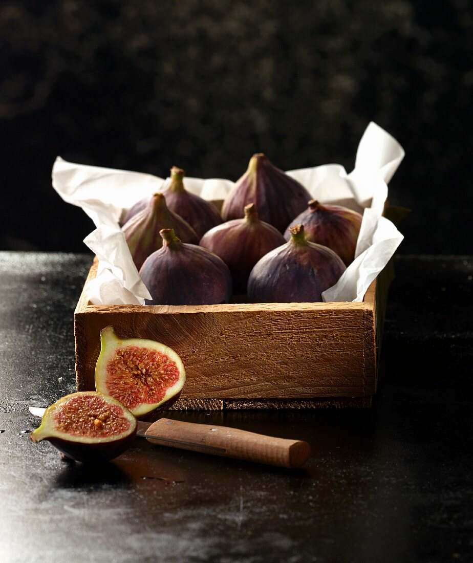 Fresh figs in a wooden crate with paper with a halved fig and a knife in the foreground