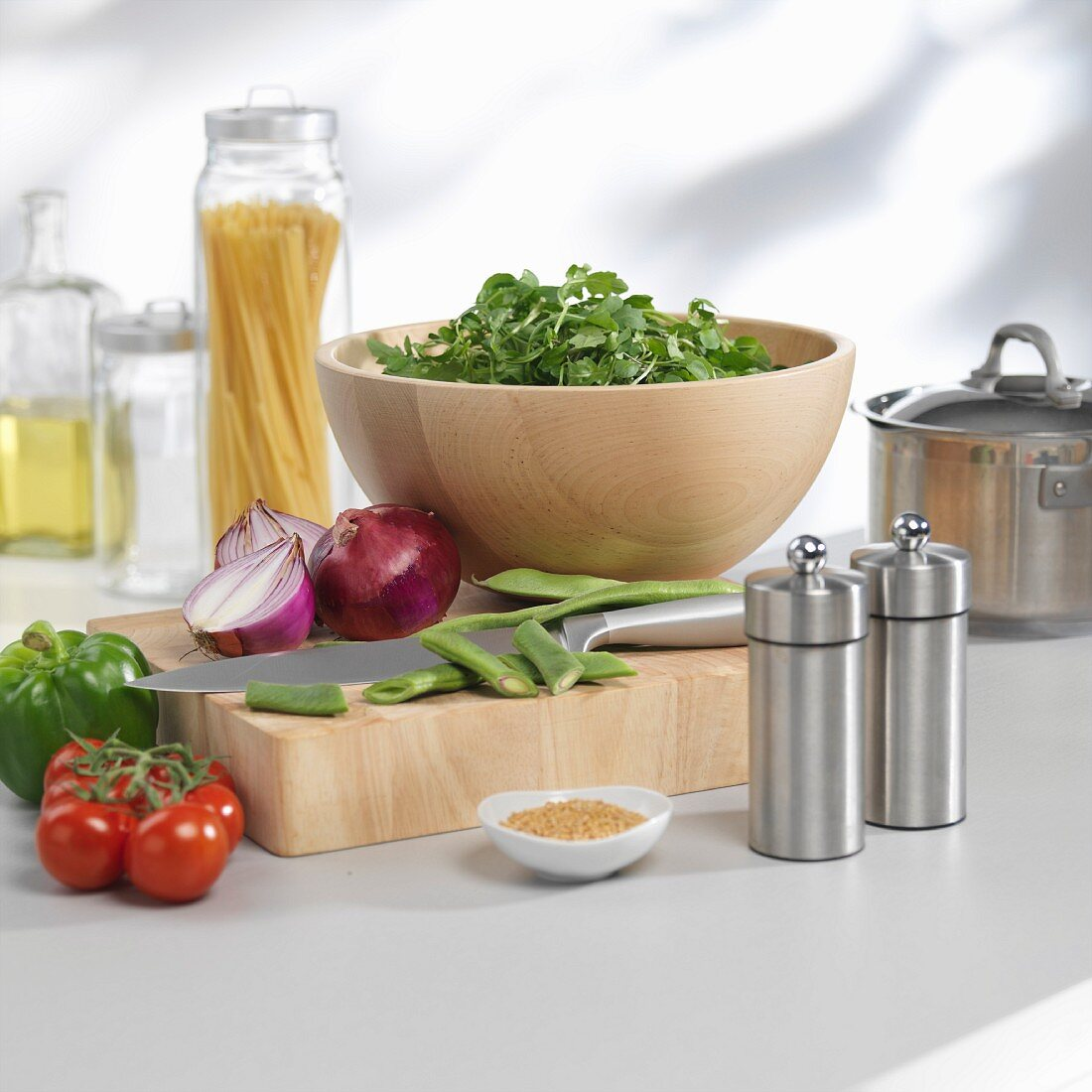 A bowl of lettuce and vegetables on a chopping board