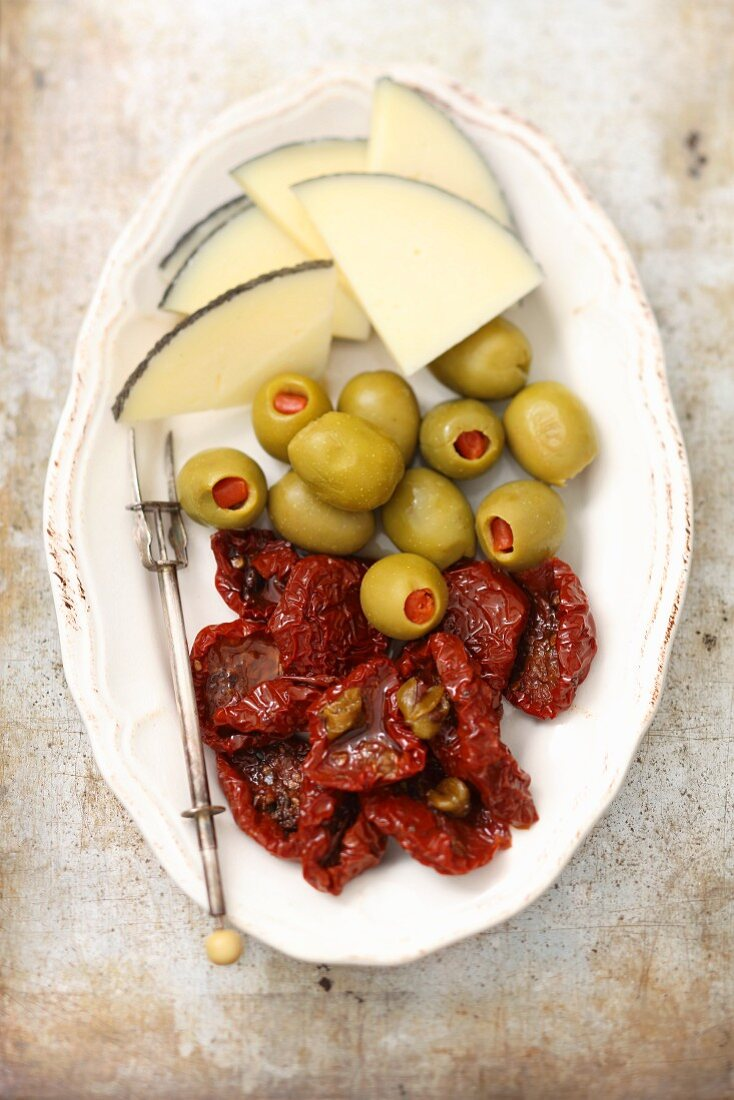 A tapas plater with cheese, olives and dried tomatoes