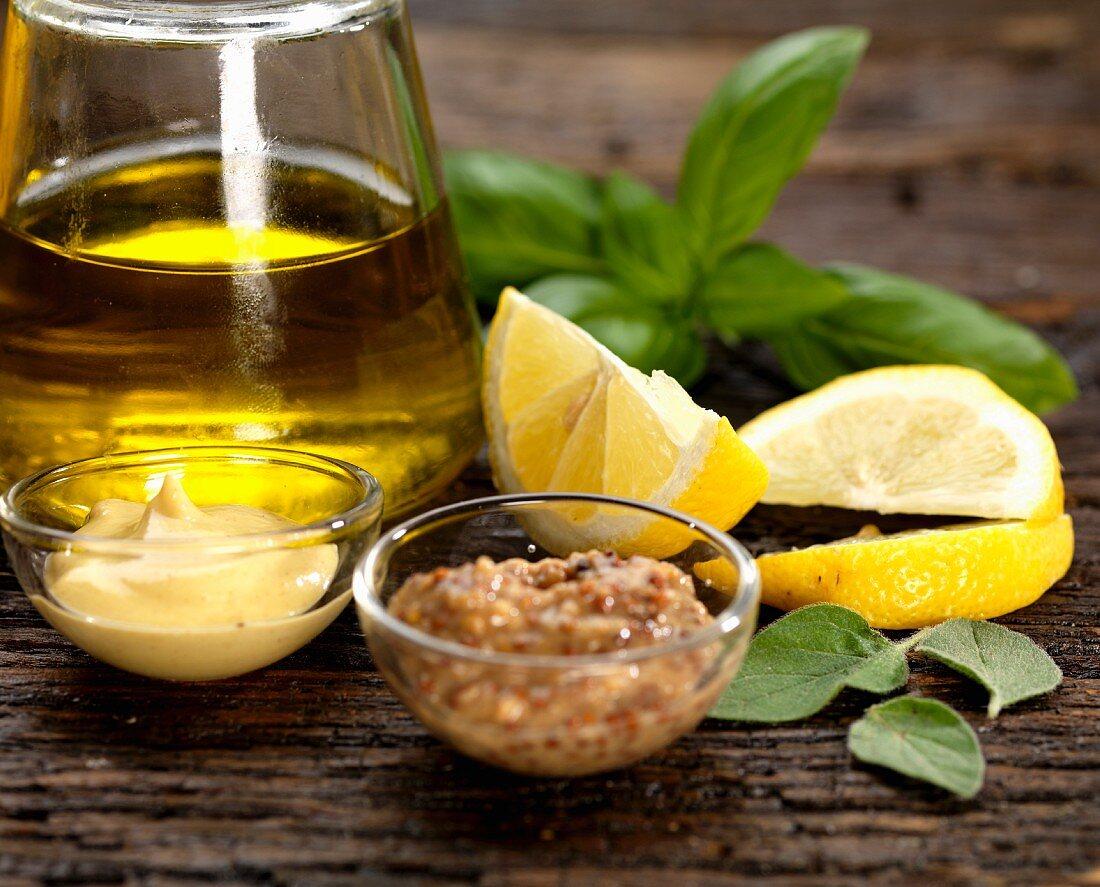 Ingredients for salad dressing with olive oil, Dijon mustard, hot mustard, lemon, basil and sage